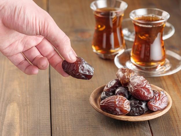 Dates avec du thé noir sur une table en bois. nourriture traditionnelle de l'iftar pendant le ramadan.