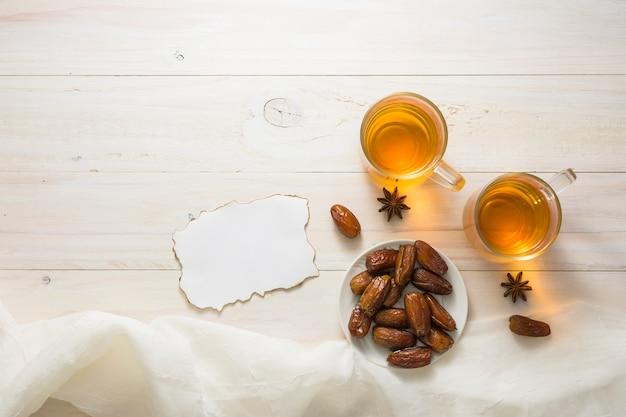 Dates fruits sur assiette avec du thé et du papier