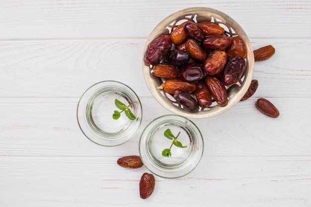 Dates fruits sur petite assiette avec de l'eau dans des bols