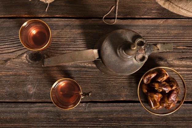 Dates de fruits avec des verres à thé sur une table en bois