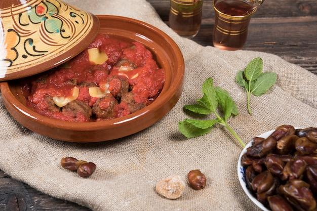 Dates fruits avec viande et thé sur table