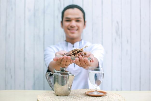 Dates sur les mains de l'homme musulman avec théière et verre rempli d'eau sur la table