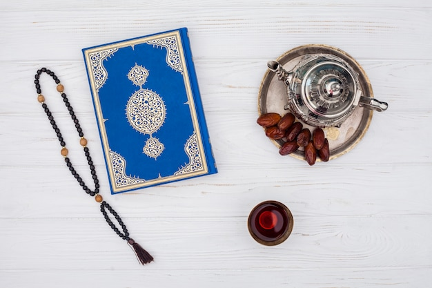 Dates sèches près de la théière, tasse de thé et livre près de perles