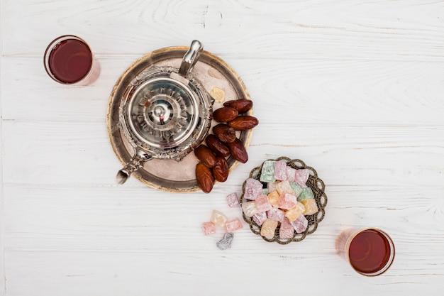 Dates sèches près de la théière, des tasses de thé et des délices turcs