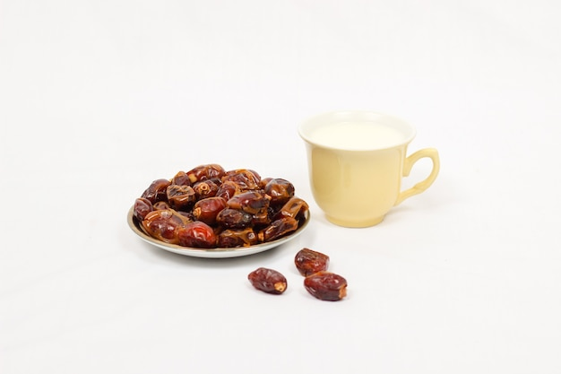 Dates et un verre de lait isolé sur fond blanc