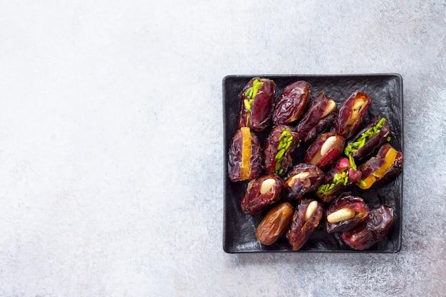 Dattes farcies aux noix et garniture de fruits confits sur une pierre ou une ardoise