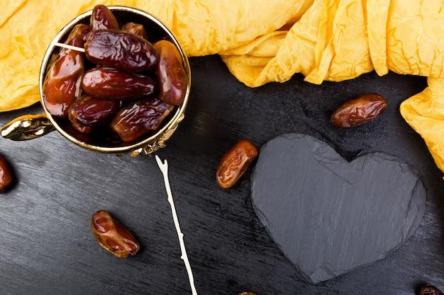 Dattes de fruits secs dans une tasse dorée près de coeur noir ardoise