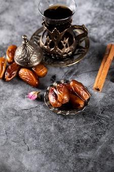 Dattes orientales dans une soucoupe de style ethnique avec un verre de thé et des bâtons de cannelle