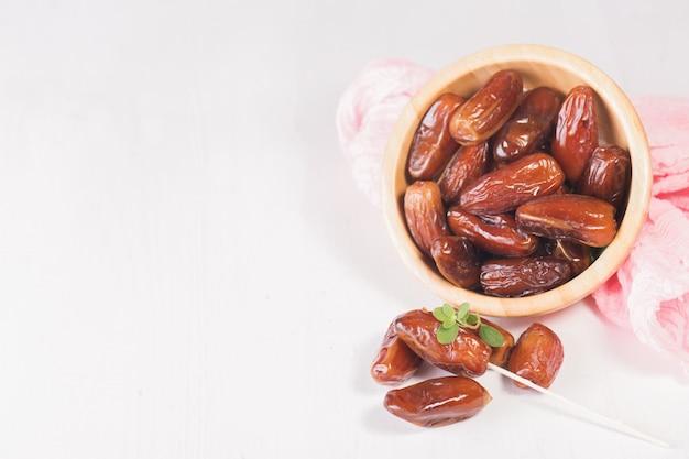 Dattes séchées sucrées crues dans un bol en bois