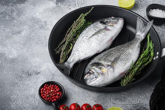 Daurade crue ou poisson cru dorado sur une poêle à griller avec des ingrédients sur fond texturé blanc gris, espace de vue latérale pour le texte.