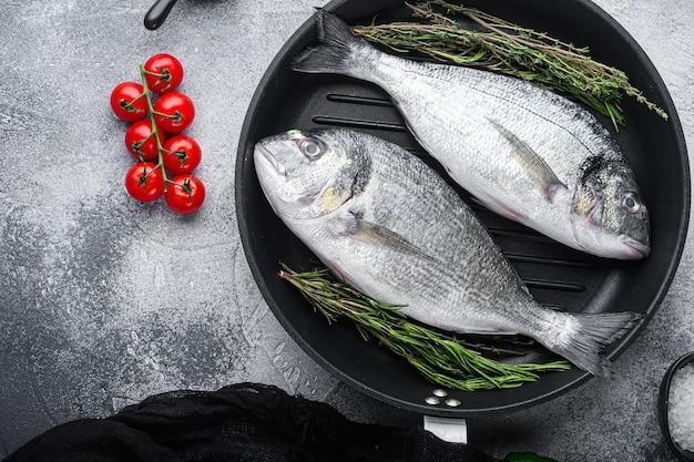 Daurade ou dorado poisson cru sur la lèchefrite avec des ingrédients sur fond texturé blanc gris, espace vue de dessus pour le texte.