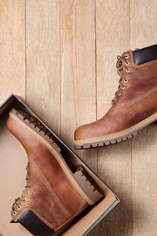 Déballage de bottes imperméables en cuir marron homme pour randonnées hivernales ou automnales dans une boîte. mode masculine, chaussures à la mode. vue de dessus flatlay