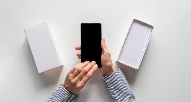 Déballage d'un nouveau smartphone sur un tableau blanc. mains féminines tenant un smartphone moderne avec écran blanc. concept d'achat en ligne. vue de dessus.