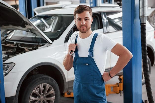 Debout avec une clé à la main. employé dans l'uniforme de couleur bleue travaille dans le salon automobile