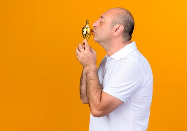 Debout dans la vue de profil casual man holding and kissing gagnant cup isolé sur mur jaune avec espace copie
