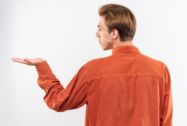 Debout derrière la vue jeune beau mec vêtu d'une chemise rouge faisant semblant de tenir quelque chose d'isolé sur un mur blanc