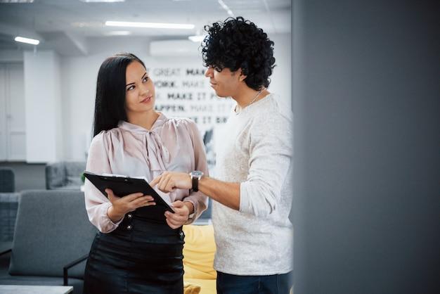 Debout et parler de quelques corrections. un mec bouclé et une fille brune discutent des détails du contrat dans un bureau moderne