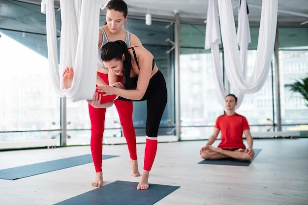 Debout près de l'enseignant. femme brune n leggings essayant le yoga aérien debout près de professori