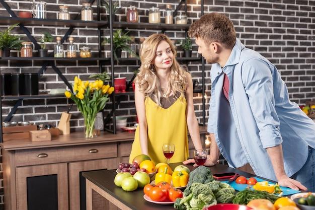 Debout près de la table. beau jeune couple debout près de la table dans la cuisine, boire du vin et préparer le dîner