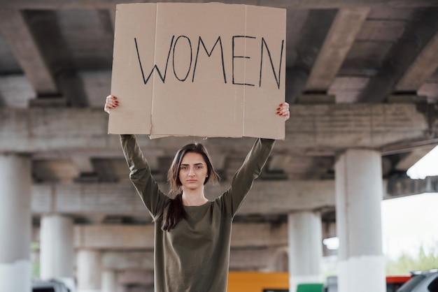 Debout seul. jolie femme en vêtements décontractés avec affiche féministe à la main en mains