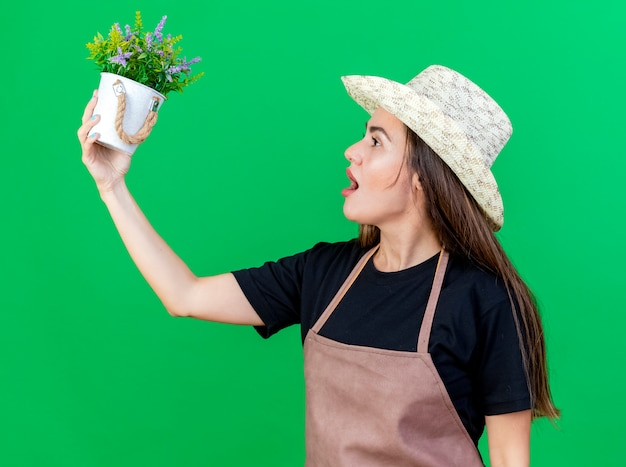 Debout en vue de profil belle fille de jardinier en uniforme portant un chapeau de jardinage soulevant et regardant fleur en pot de fleurs isolé sur vert