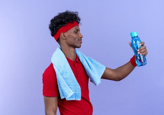 Debout en vue de profil heureux jeune homme sportif portant un bandeau