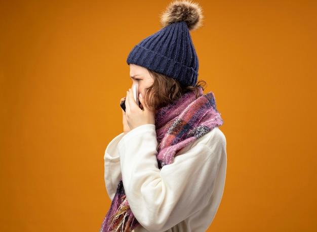 Debout en vue de profil jeune fille malade portant une robe blanche et un chapeau d'hiver avec écharpe parle au téléphone isolé sur orange