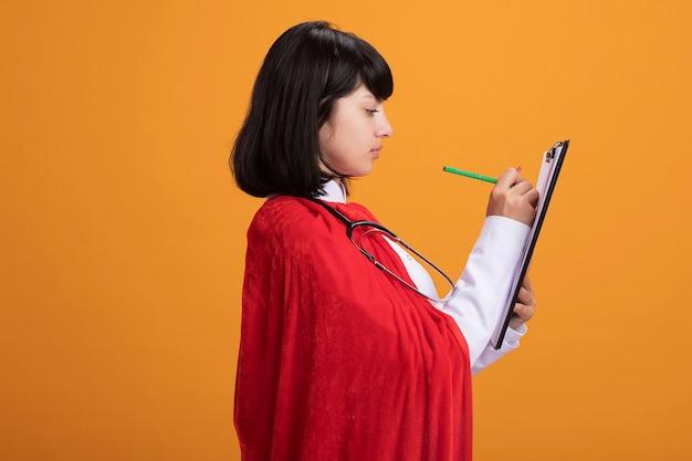 Debout en vue de profil jeune fille de super-héros portant un stéthoscope avec une robe médicale et une cape d'écrire quelque chose sur le presse-papiers