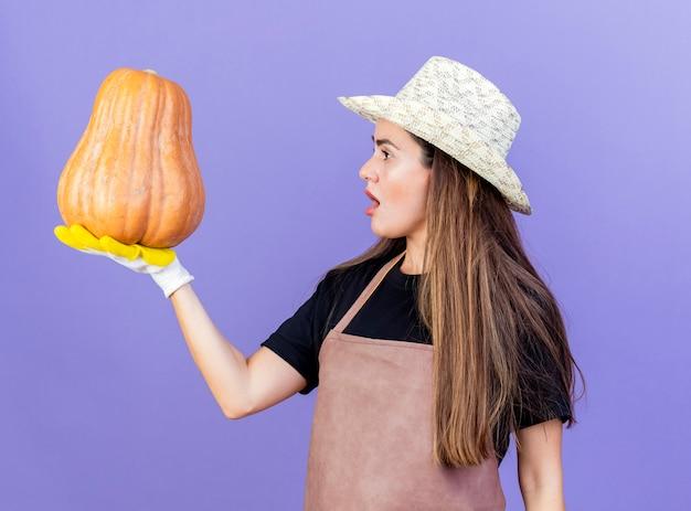 Debout en vue de profil surpris belle fille de jardinier en uniforme portant un chapeau de jardinage et des gants tenant et regardant la citrouille isolé sur fond bleu
