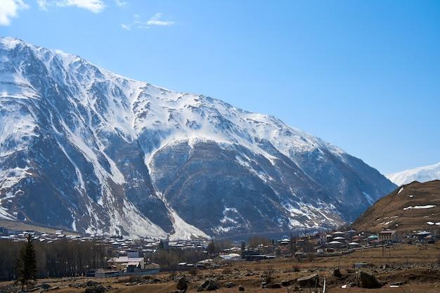 Début du printemps. le village est dans les montagnes. bonnets de neige au sommet des montagnes. petit village au pied.