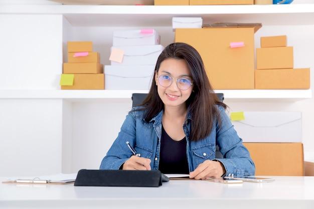 Début du succès de la jeune femme d'affaires avec une nouvelle commande du client, petit travaillant au bureau à domicile