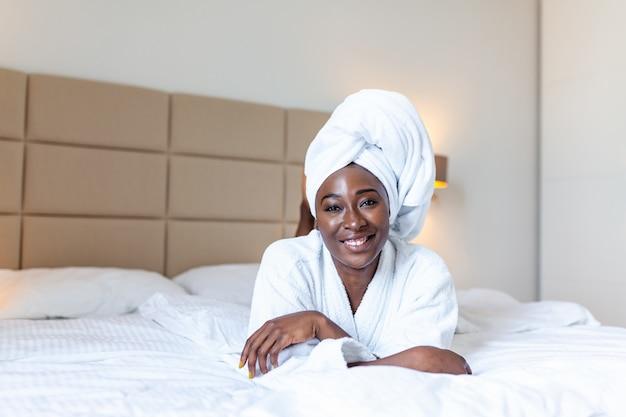 Un début de journée positif. souriante jeune femme africaine allongée sur le lit en peignoir.