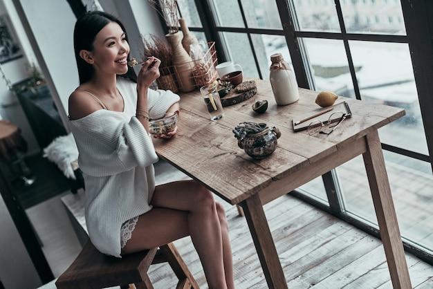 Début de journée sain. vue de dessus d'une jeune femme séduisante mangeant un petit-déjeuner sain