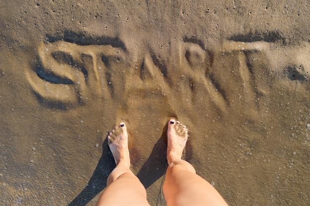 Début de texte écrit dans le sable sur la plage de la mer et les pieds nus de la femme debout devant le mot