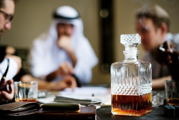 Décanteur de whisky avec des hommes d'affaires en arrière-plan
