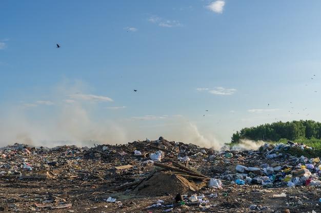Décharge de la ville avec différents déchets brûle un jour d'été ensoleillé