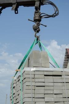 Déchargement de dalles de pavage d'un camion. des hommes déchargent des dalles de pavage à l'aide d'un manipulateur. les travailleurs déchargent les matériaux de construction d'une grosse machine.