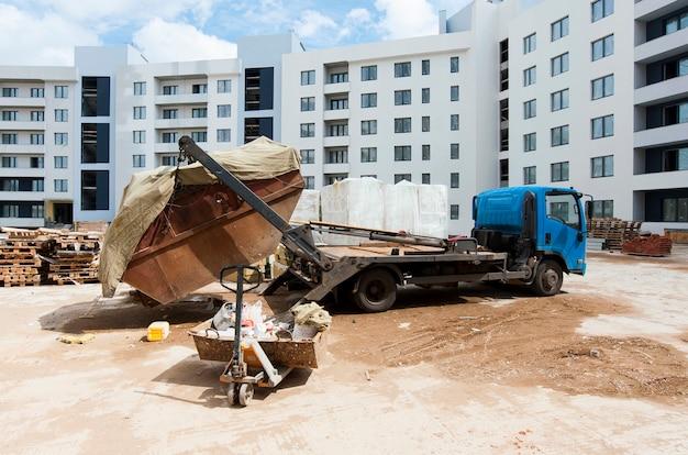 Déchargement de la machine qui a livré les marchandises au chantier de construction à la construction monolithique