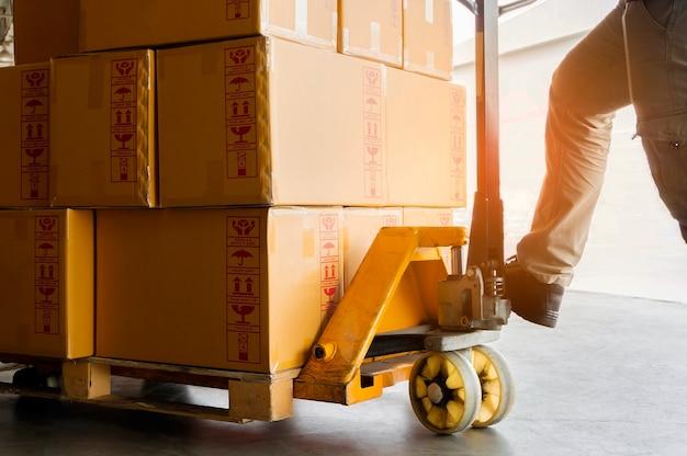 Déchargement des marchandises d'expédition des travailleurs avec transpalette manuel