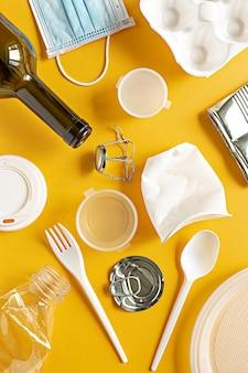 Déchets de divers matériaux en plastique métal et autres pour le recyclage à plat sur fond jaune
