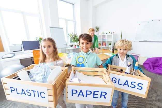 Déchets. trois élèves intelligents diligents tenant des boîtes avec différents déchets après le tri