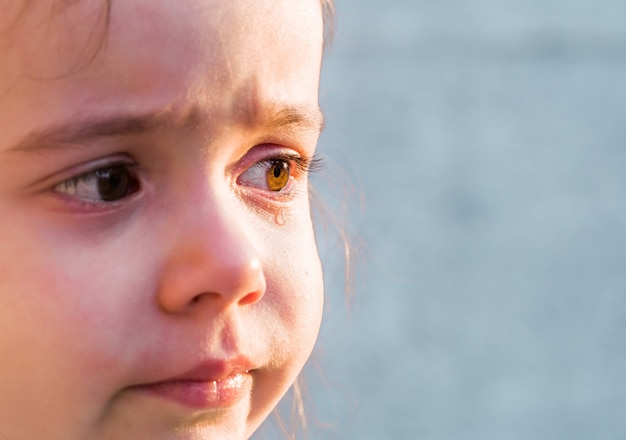 Déchire les émotions d'une petite fille, sur l'herbe grise