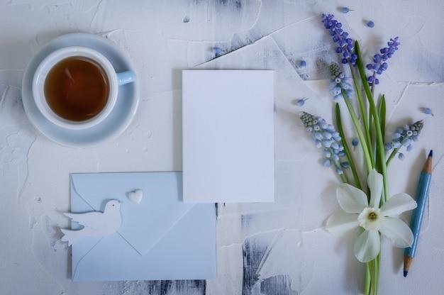 Déclaration d'amour. fleurs de printemps avec du papier pour le texte et deux oiseaux en bois et coeur. concept de mariage, de fiançailles ou de fiançailles. copiez l'espace, vue de dessus. carte de voeux.