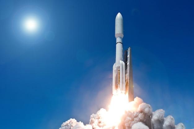Décollez la fusée spatiale sur un fond de ciel bleu et de soleil éléments de cette image fournis par la nasa