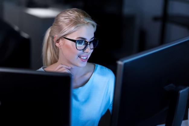 Décomposer la tâche. souriant charmant programmeur qualifié assis au bureau et utilisant des ordinateurs tout en travaillant sur la résolution des codes de mot de passe