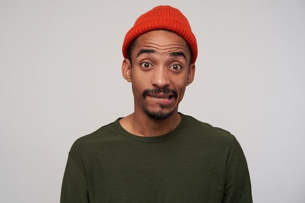 Déconcerté jeune homme barbu aux cheveux noirs avec une peau foncée portant un chapeau rouge tout en posant sur blanc, mordant la lèvre inférieure et soulevant confusément les sourcils