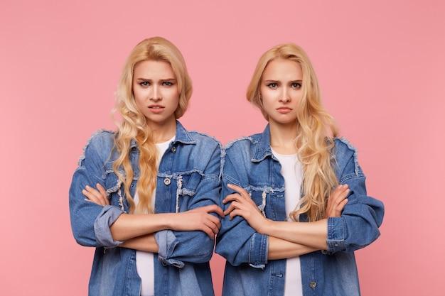 Déconcerté de jeunes belles sœurs blondes aux cheveux longs gardant les mains croisées tout en regardant sévèrement la caméra et en fronçant les sourcils, posant sur fond rose