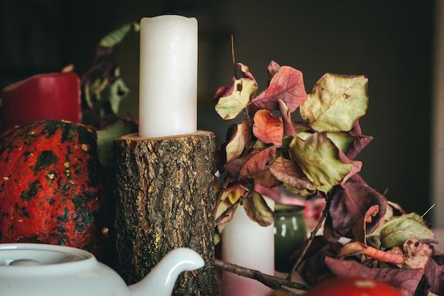 Décor d'automne avec des bougies citrouilles et de la vaisselle