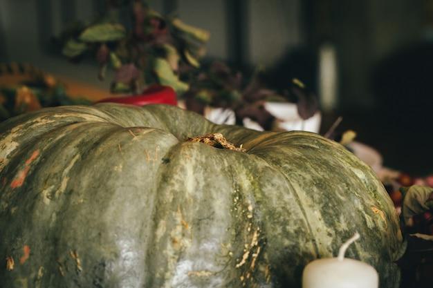 Décor d'automne avec citrouille, bougies et vaisselle