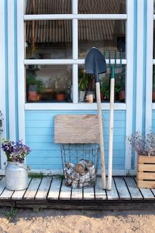 Décor d'automne confortable porche en bois de maison avec des outils de jardin